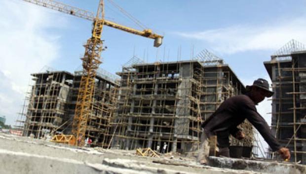 Pekerja konstruksi di depan bangunan yang sedang berlangsung pembangunannya (foto : Tempo)